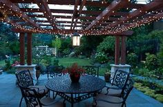 The iron furniture brings classic sense of timelessness to this outdoor seating area, while the fairy lights add a modern whimsical touch. By Paul Moon Design in Seattle, WA.