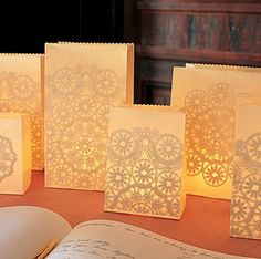 DIY with white paper bag. Glue on paper dollies and place sand on the bottom of each bag and then place a tea light candle in the center!