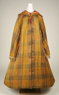 Plaid silk and cotton cloak, American, mid 19th c. Components are cloak with sleeves, cape, hood. Linings are silk and cotton. Braid trim from shoulder to opening for arm, fringed trim on edge of cape, chenille tassels on hood. MET