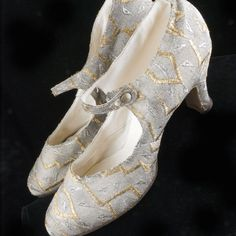 A stunning pair of 1920's silver lame shoes with silver and gold metallic satin stitch embellishments. Fully lined in ivory colored kid leather. Embossed brass buttons close the straps. Tan leather soles. Marked Made in England *6 1/2