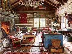 Ralph Lauren's COLORADO GUEST CABIN LIVING ROOM Overlooking the cabin's living room is a chandelier made with naturally shed elk antlers; beside the hearth, a woven-twig rocking chair is draped with a vintage Capps Indian-trade blanket, and an antique New Mexico pine table stands atop an early-20th-century Navajo rug.