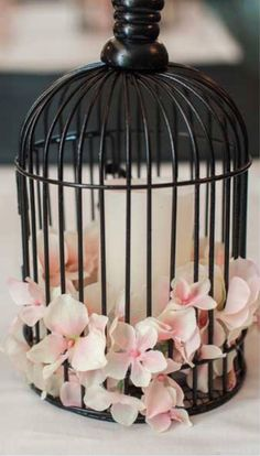 Birdcage centerpiece inspiration. I would do a white cage with bright flowers around a white pillar candle.