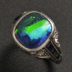 Art Deco Platinum, Black Opal, Sapphire, and Diamond Ring, Tiffany & Co., bezel-set with a black opal measuring approx. 11.09 x 10.75 x 4.76 mm, flanked by baguette-cut sapphires, old European-cut diamond accents, millegrain and engraved details, size 6, signed.