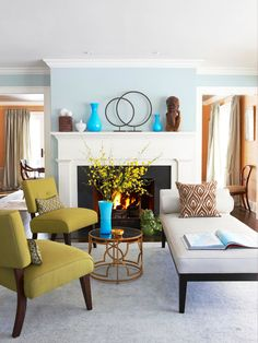 To maintain a restrained yet colorful scheme, use a vibrant color for accents and a lighter, less intense version for paint on the walls. Turquoise vases add the pop to this living room, while a soft sky blue envelopes the room in calm sophistication. The turquoise also ties the fireside sitting area to the other arrangement of furniture with the peacock blue chair.
