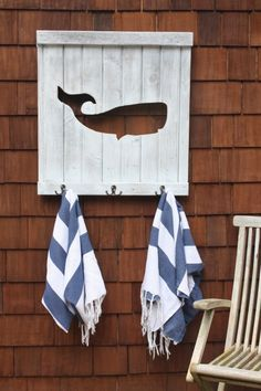 Old wood repurposed as poolside whale towel rack
