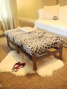 Get a Goodwill coffee table, cover with some batting and fabric, and have the coffee table/ottoman you need!
