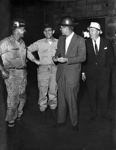 John F. Kennedy, wearing hard hat, talks with miners in West Virginia during the Presidential Primary campaign in April 1960.