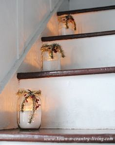 """Mason Jars filled with flour for """"snow"""" and a votive tucked inside. Decorate with tinsel and berries and line them up on the stairs."""