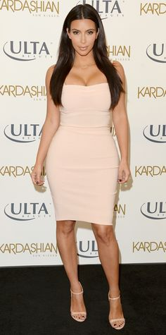 """Kim Kardashian promoted her """"Sun Kissed"""" tanning line in a skin-skimming blush-pink Bec & Bridge strapless dress, with nude ankle-strap sandals."""