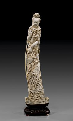 """ANTIQUE CHINESE IVORY IMMORTAL BEAUTY   象牙雕花籃仕女  Tall and very elaborately carved, antique Chinese ivory figure; of a celestial beauty, carrying a basket of flowers, with a phoenix by her side, and all atop a lotus motif base; Circa 1900; H: 29 1/2"""", lacquered wood stand with ivory rail"""