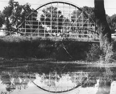 A roller coaster from Playland Park in Council Bluffs, Iowa, is reflected in a water hole at Dodge Park in October 1959. THE WORLD-HERALD