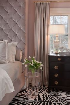 Suzie: Tiffany Eastman Interiors - Blush pink bedroom with blush pink walls paint color, blush pink velvet tufted tall headboard bed, blush pink bedding, acrylic accent table, zebra rug, glossy black chest and gray linen curtains