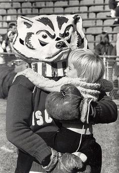 UW-Madison mascot Bucky Badger hugs a small child. 1967.