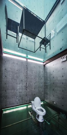 Glass floors allow residents to look down from a dining table into a toilet inside this windowless concrete house in Shanghai.
