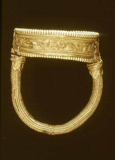 Gold finger-ring; rounded hoop, covered with fine twisted gold wires; at either end is soldered a ring of leaves and a palmette in filigree; deep oval bezel with a filigree design of rosettes and spirals (partly broken away); the sides of the bezel are decorated with tendrils in filigree within twisted wires; on the underside of the bezel are the remains, of four palmettes in filigree arranged round a hole.