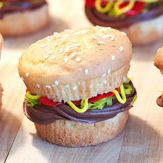 "Cupcake Burger!!!    * Slice each cupcake in half.  * Add a circle of chocolate frosting on each ""bottom bun"".  * Add colored coconut ""lettuce"".  * Pipe on red and yellow frosting to simulate ketchup and mustard."