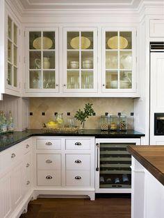 White cabinets, glass upper doors, black granite countertop, butcher block island, tile backsplash...