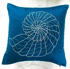 dark blue throw pillow with silver shell embroidery