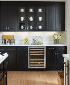 Black cabinets, white counter, white subway tile backsplash & light oak wood floors.  Now this I could do.