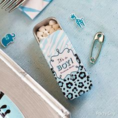Tins of candy and tiny diaper pin charms make cute table details! Click for more wildly wonderful blue safari baby shower ideas.