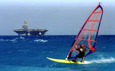 Cowabunga!!! Wind surfers in Greece ride the waves while USS Theodore Roosevelt (CVN 71) rolls by