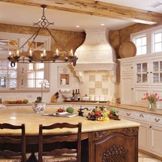Frech Style #Kitchen | Exposed ceiling beams, wrought iron, and hand-carved wood accentuate its old-world flair.