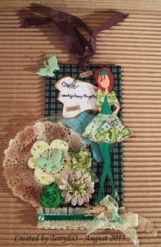 This is a Julie Nutting Prima doll tag with a fabric background.