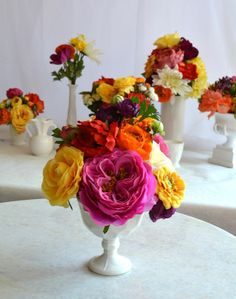 Use a variety of white ceramic vases to hold colorful blooms for a lovely centerpiece #afloral #whitewedding # artificialflowers #weddingflowers