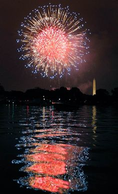 Fireworks illuminate the night sky and are reflected in the Potomac River with the Washington Monument at right on Monday, July 4, 2011, in Washington, D.C.