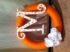 Foam wreath wrapped in yarn. Painted wooden letter (acrylic and paint pen). Felt flowers. All hot glued together!!