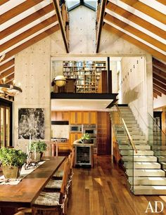 At a ranch in Southern California, an ironwood table and chairs decorate the great room's dining area; Dogger, by Elliott Puckette, hangs on the concrete column. The stairs lead to the library, which is suspended above the kitchen; the range, ovens, and wine refrigerator are by Viking.Pin it.