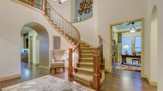 The elegant #curved #staircase in this Bridges of Las Colinas #model #home adds a dose of luxury to your spacious #foyer.