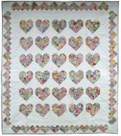 Emily's Heart Quilt : This Heart Quilt is a bride's quilt for my daughter. Emily likes hearts, so I decided to figure out a heart pattern rather than the classic wedding ring or nosegay. I had vintage squares from the 30′s & 40′s & they ended up being perfect. It's made up of 2 different heart patterns, separated by white sashing strips. The hearts are quilted with a diagonal grid in the heart & flowers in the white corners. The border is quilted with hearts/flowers; the corners w/ bows/hearts.