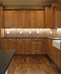 Shaker style Knotty Alder cabinets, geometric crown moulding, white farmhouse kitchen sink, black granite counter, under-cabinet lighting.