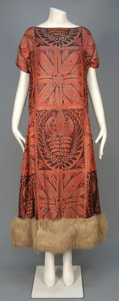 ART DECO JACQUARD DRESS with METALLIC THREADS, 1920s. Stylized floral in black, grey and metallic gold on pink having short sleeve, full skirt with dropped waist, side gathers and fur hem band.