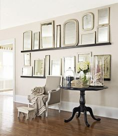 Mirror collage on plate rails, mounted above a chair/table vignette creates drama.. using black frames to reference and juxtapose the roundness of the black table and the roundness is smart