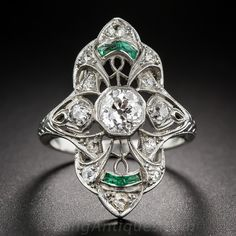 A .60 carat old mine-cut diamond, set in a finely milgrained, octagonal bezel setting, is the sparkling center of attention of this distinguished and highly distinctive Art Deco dinner ring. The shapely outline of the ring frames a sinuous openwork design glittering with twelve small old mine-cut and single-cut diamonds accented at each end with a pair of bright-green faceted calibre emeralds. Hand engraving adorns all three sides of the upper ring shank, c 1925