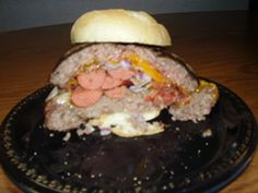 """The legendary """"Nice 2 Meat You"""" burger is a 1 ¼ lb. hamburger, stuffed with a ½ lb. hot dog, and ¼ lb. of bacon, cheese, and onions."""