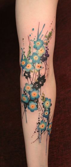 Watercolor flowers tattoo on arm.