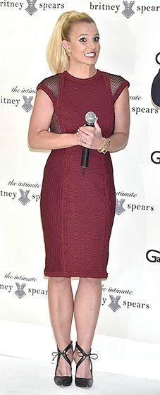 Britney Spears looked magnificent in a figure-flattering maroon dress with mesh detailing along the shoulders to promote her new line of lingerie.