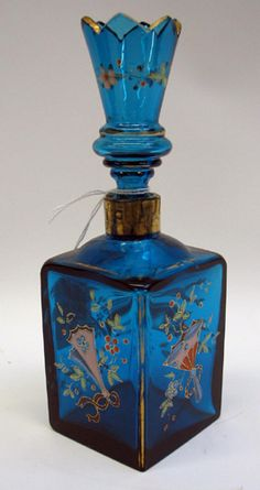 A MOSER GLASSWORKS ENAMELED BLUE GLASS PERFUME BOTTLE, in square form with fluted original stopper, hand enameled decoration of flowers, fans and plumes, gold accented. Height 7 in.