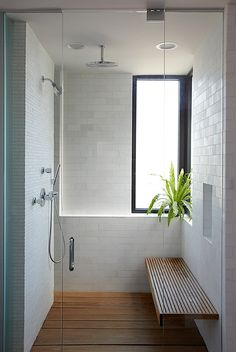 Wood floor, wood bench, and plant, in a shower. Amazing. Also love the different sized subway tiles, adds some cool optical illusion with scale.