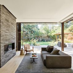The living room, with its lava-stone hearth, Imari rug by RH, vintage coffee table and Capo lounge chair by Neri & Hu for De La Espada, becomes one with the outdoor rooms thanks to folding glass doors by Southland Windows & Doors. On the deck, a conversation area is composed with RH seating surrounding a Santa Barbara fire pit. A landscape of drought tolerant plants was designed by landscape architect Richard Radford.