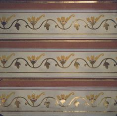 """Frieze, 1890–1900. This design simulates a stencil design and consists of three identical borders running parallel with selvedge. Latter is marked """"Robert Graves Co. 1581"""". Field is beige color with a vine in wave-like formation with single flower in orange and cinnamon. Vine and three petaled leaf between each flower in gold bronze. Narrow gold band at bottom. Graduated bands at top of henna, gold, cinnamon, and gray, respectively. Machine printed."""