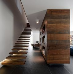 gorgeous black slate floors + amazing floating staircase + huge dividing bookcase = adore!