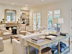 so fresh and airy. Love the furniture placement, the sofa table, the wing chairs, the mirror, the doors.......