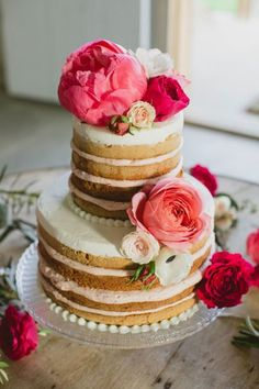 Naked wedding cake with fuchsia and peach flowers.