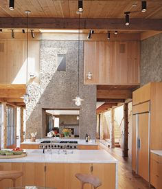 """The house has the feel of a refined barn: The kitchen flows into the dining area, then into a den. The two PISE """"chimneys"""" serve to demarcate the transitions and visually unite the space."""