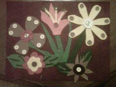 Felt flower garden. Using fabric glue, assorted cut felt pieces and buttons on a felt background.