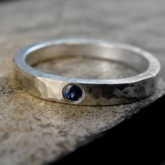 Sparkly blue sapphire is flush set into an oxidized sterling silver ring; the thick band is hammered with a rustic feel, and a dark gray patina applied.   The patina will wear to a soft gray with use, exposing the matte silver beneath.